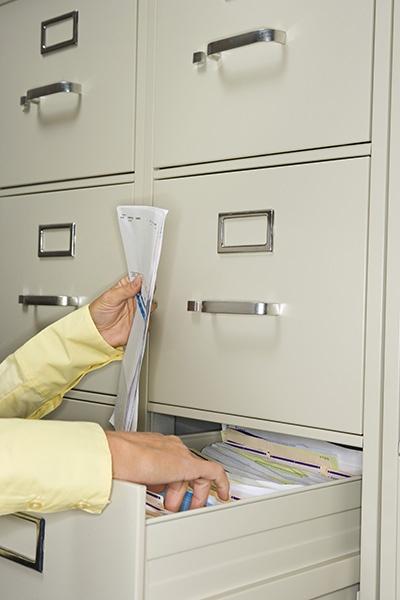 Iratszekrény nyitott fiókkal, női kéz benne dokumentummal
