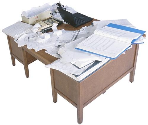 Rendetlen íróasztal a dokumentum halmok között egy laptoppal
